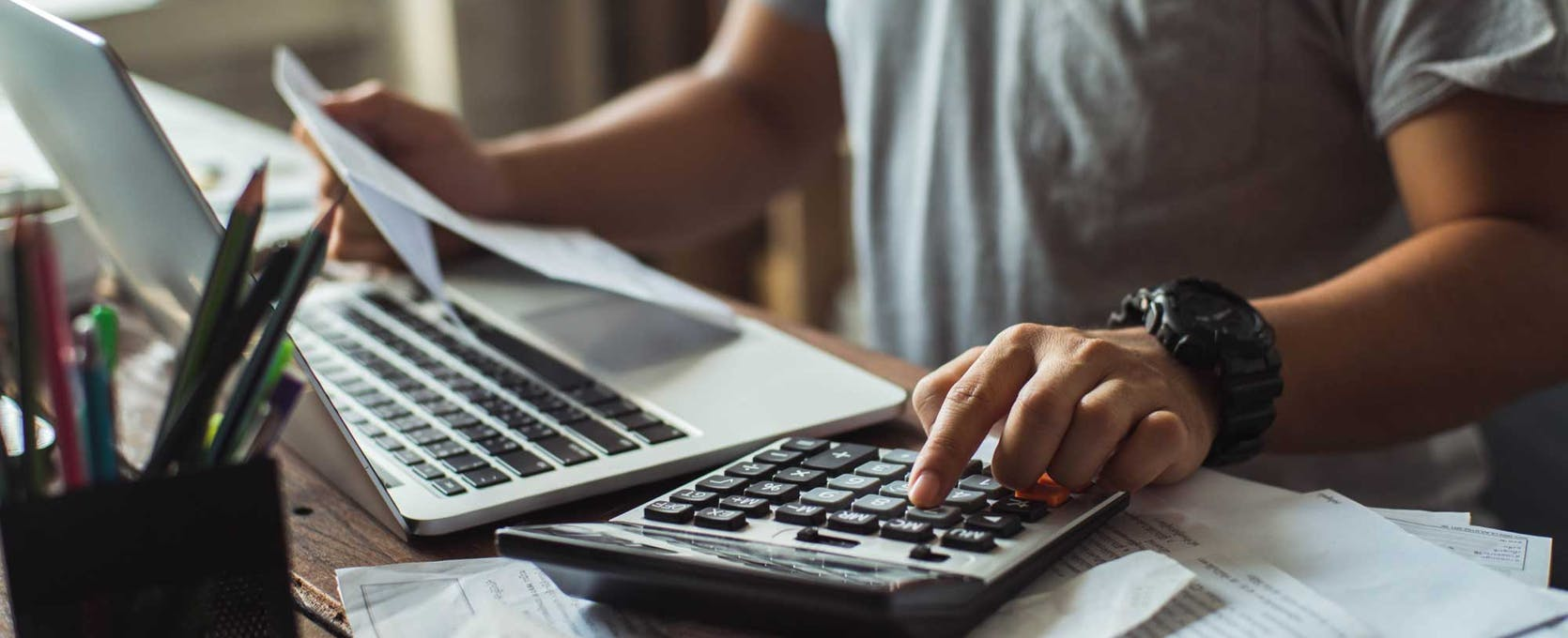 Man reconciles expense accounts with calculator and computer