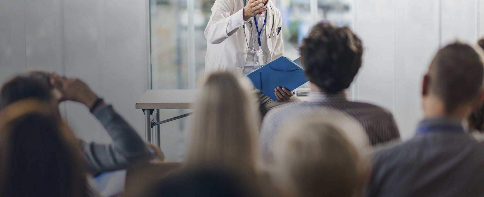 Doctor presenting information to a large crowd