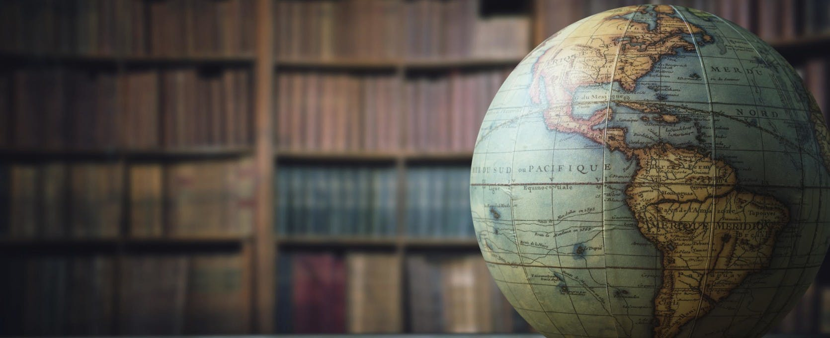 A globe resting on a desk in a library