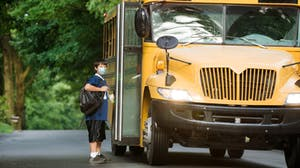 Student wears mask as he gets on the bus for school