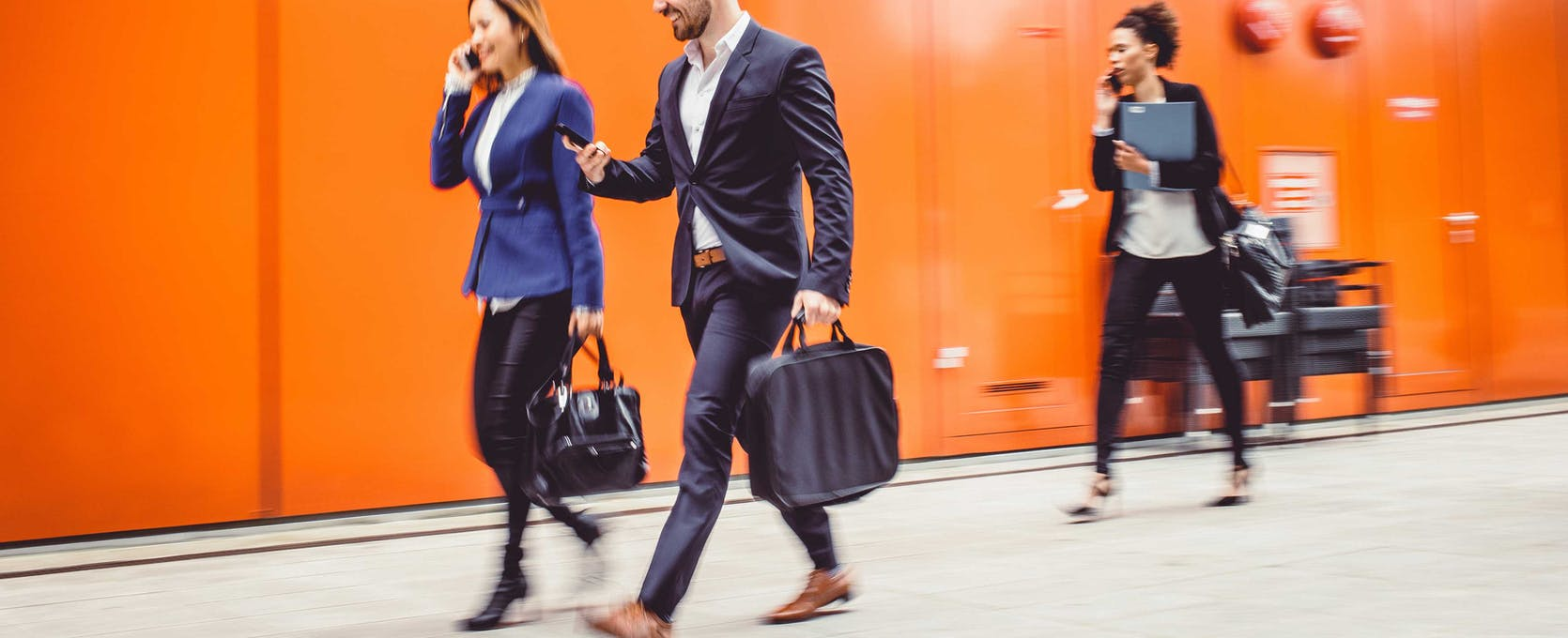 Young business professionals on their phones walking to a meeting