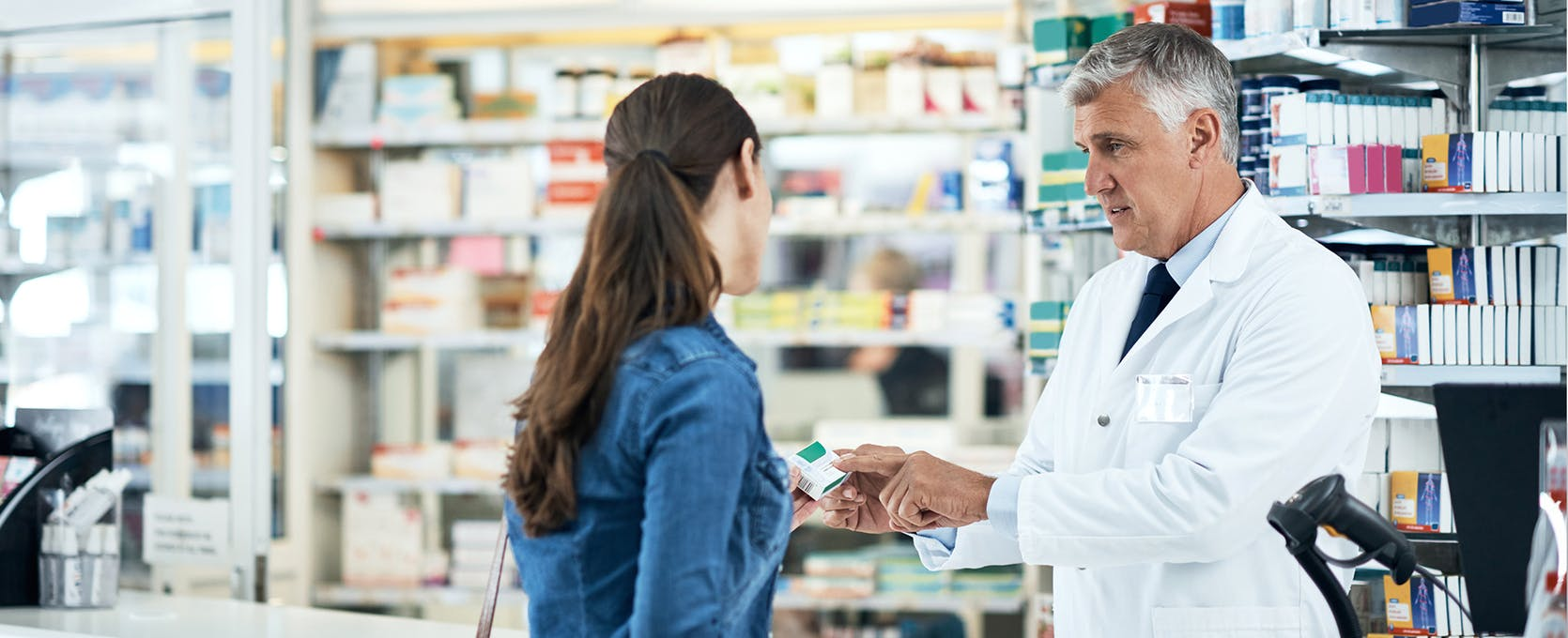 Pharmacist speaking with a customer at a pharmacy