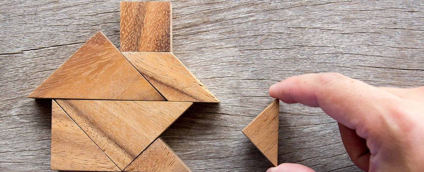 Wooden tangram puzzle in the shape of a house