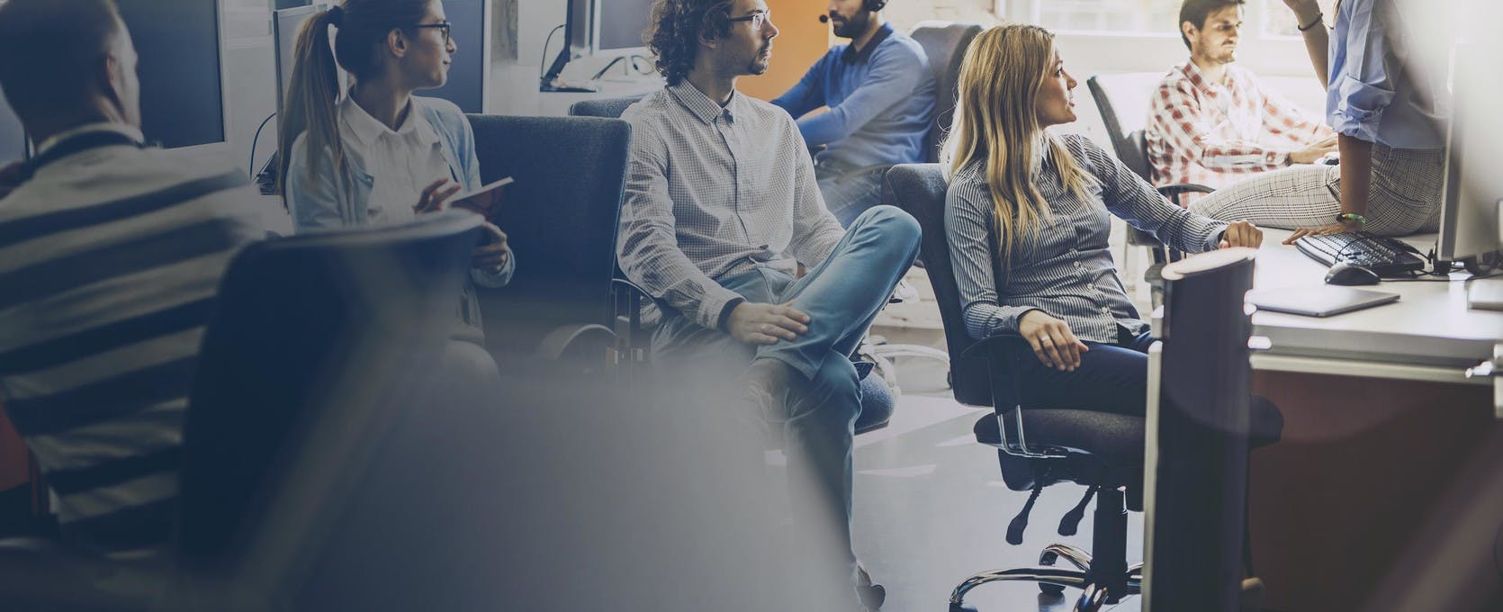 people sitting in desk chairs having a meeting