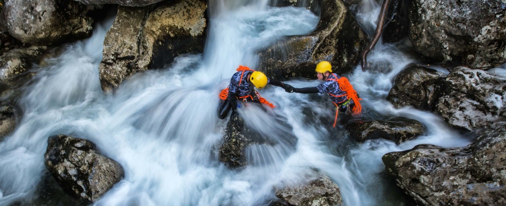 Working together to climb over slippery stream bed