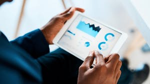 Business professional viewing data and graphs on tablet