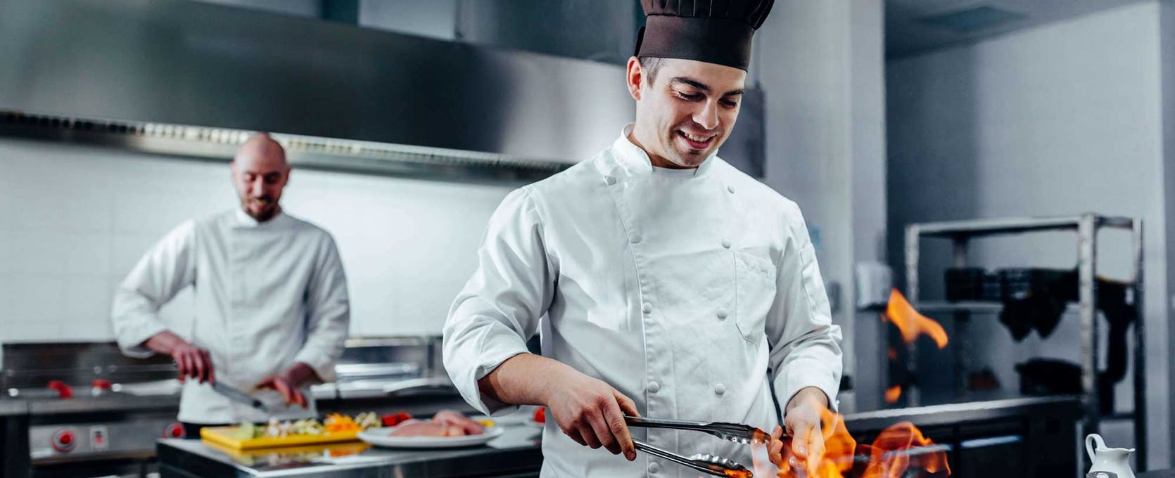 Chefs prepare meals for patron at a franchise restaurant