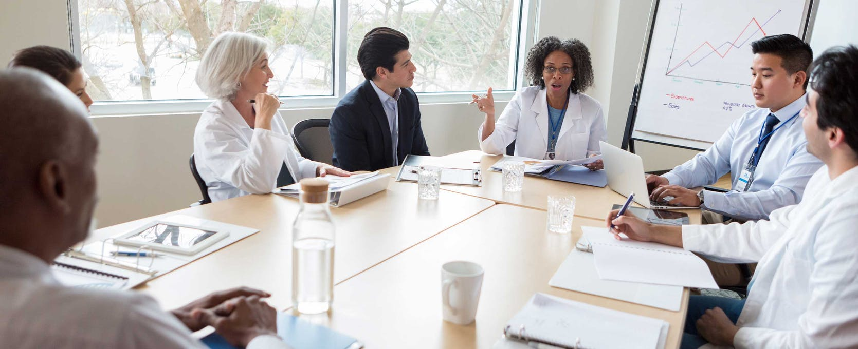 Medical management team discusses data and technology strategy in a conference room