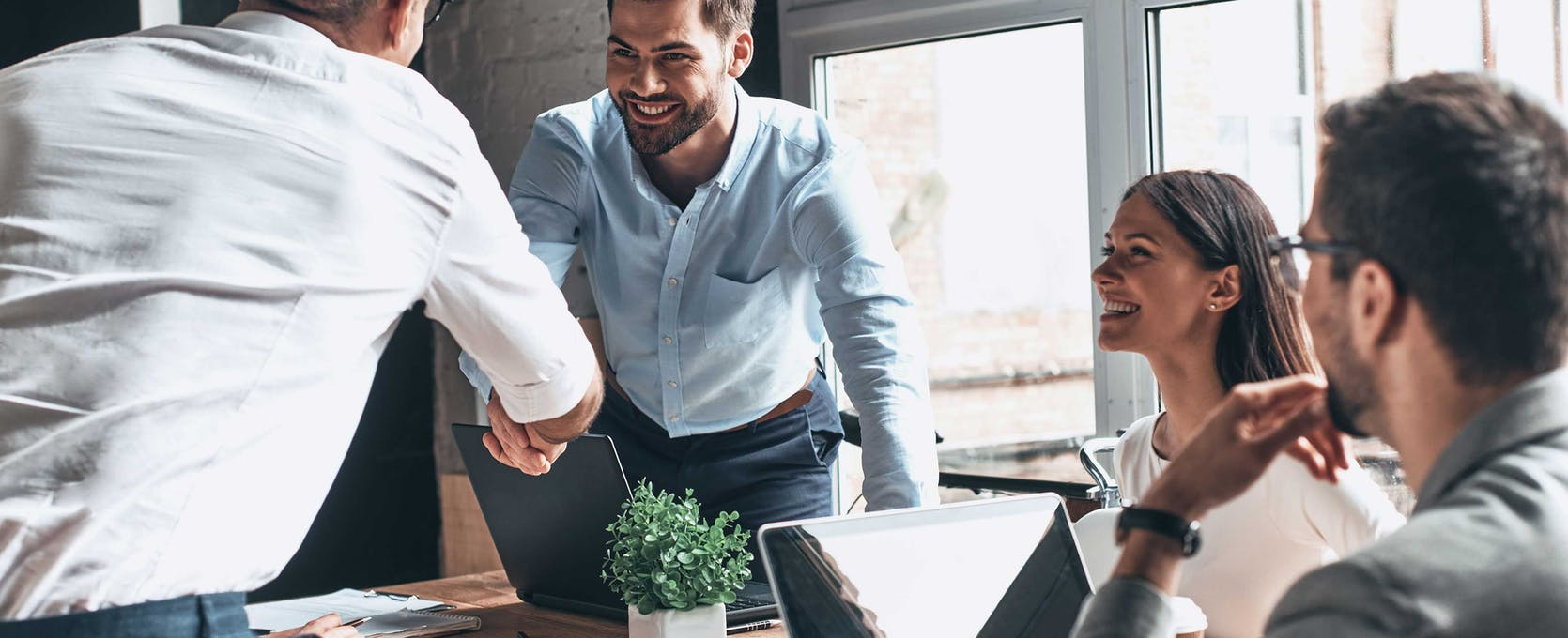 Business person is welcomed to a meeting with a handshake