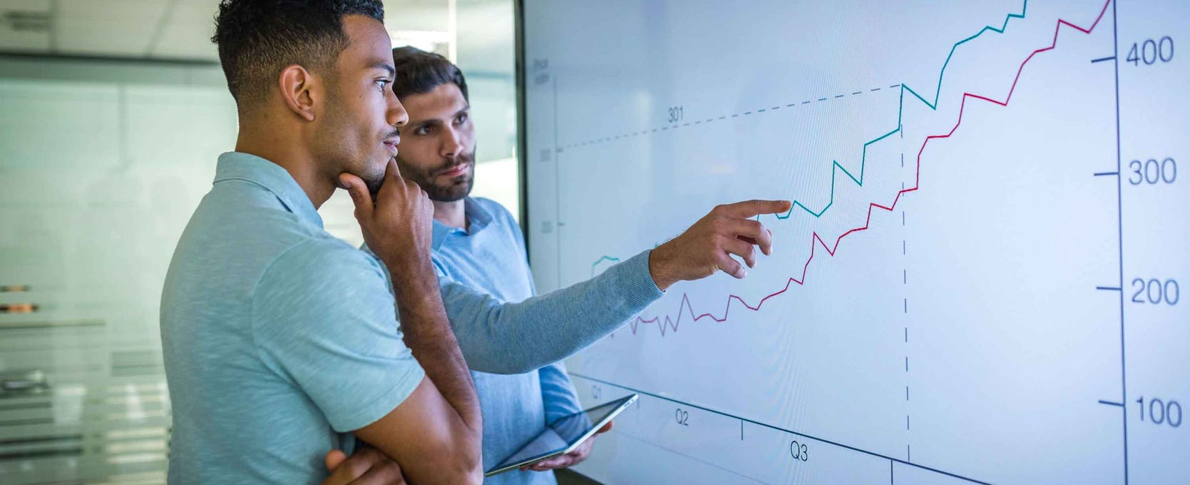 Two advisors reviewing financial services dashboard data
