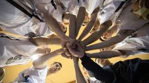 A team puts their hands in the center of a team huddle