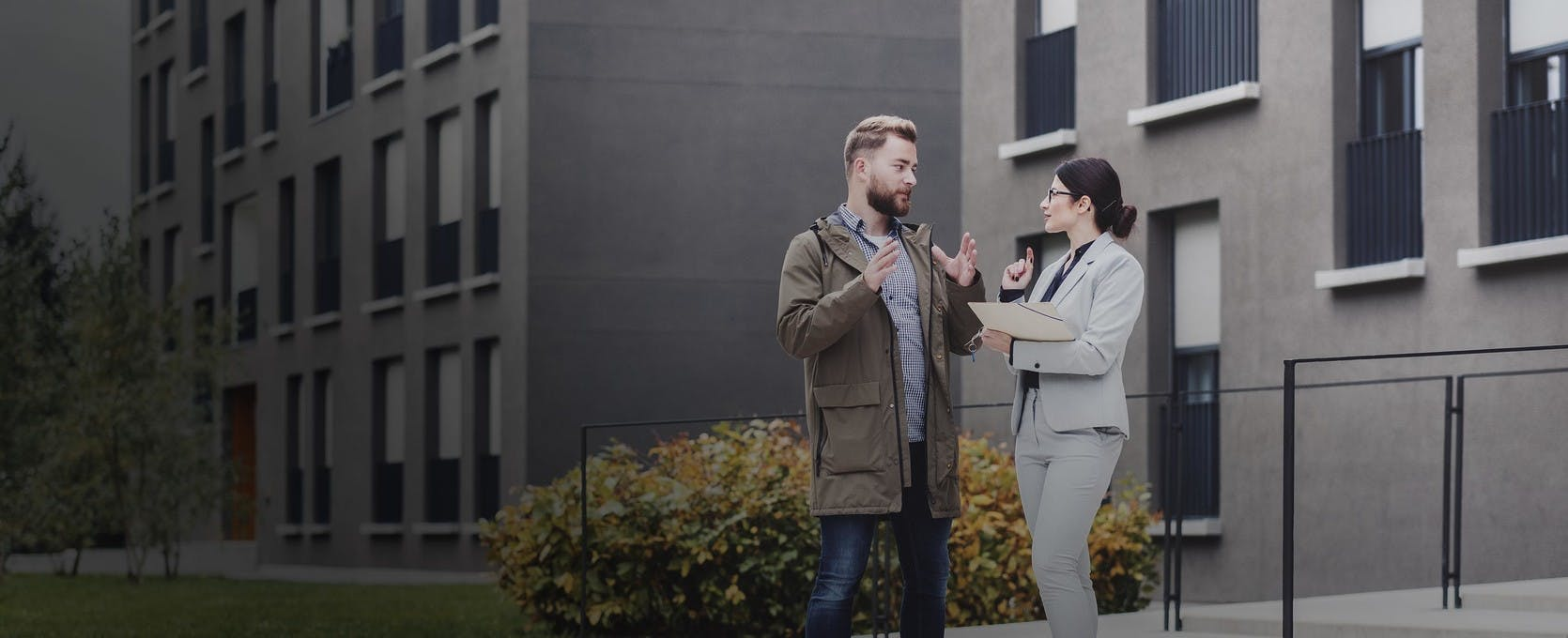 Two people outside a property discussing cost segregation