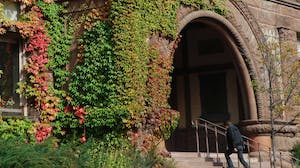 Student enters an ivy-covered building on campus