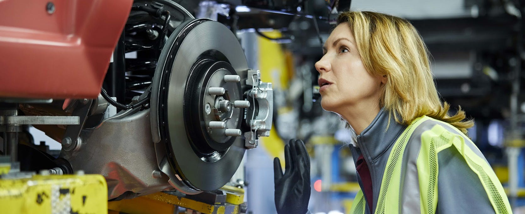 Automotive and mobility worker inspects car's drivetrain on the assembly line
