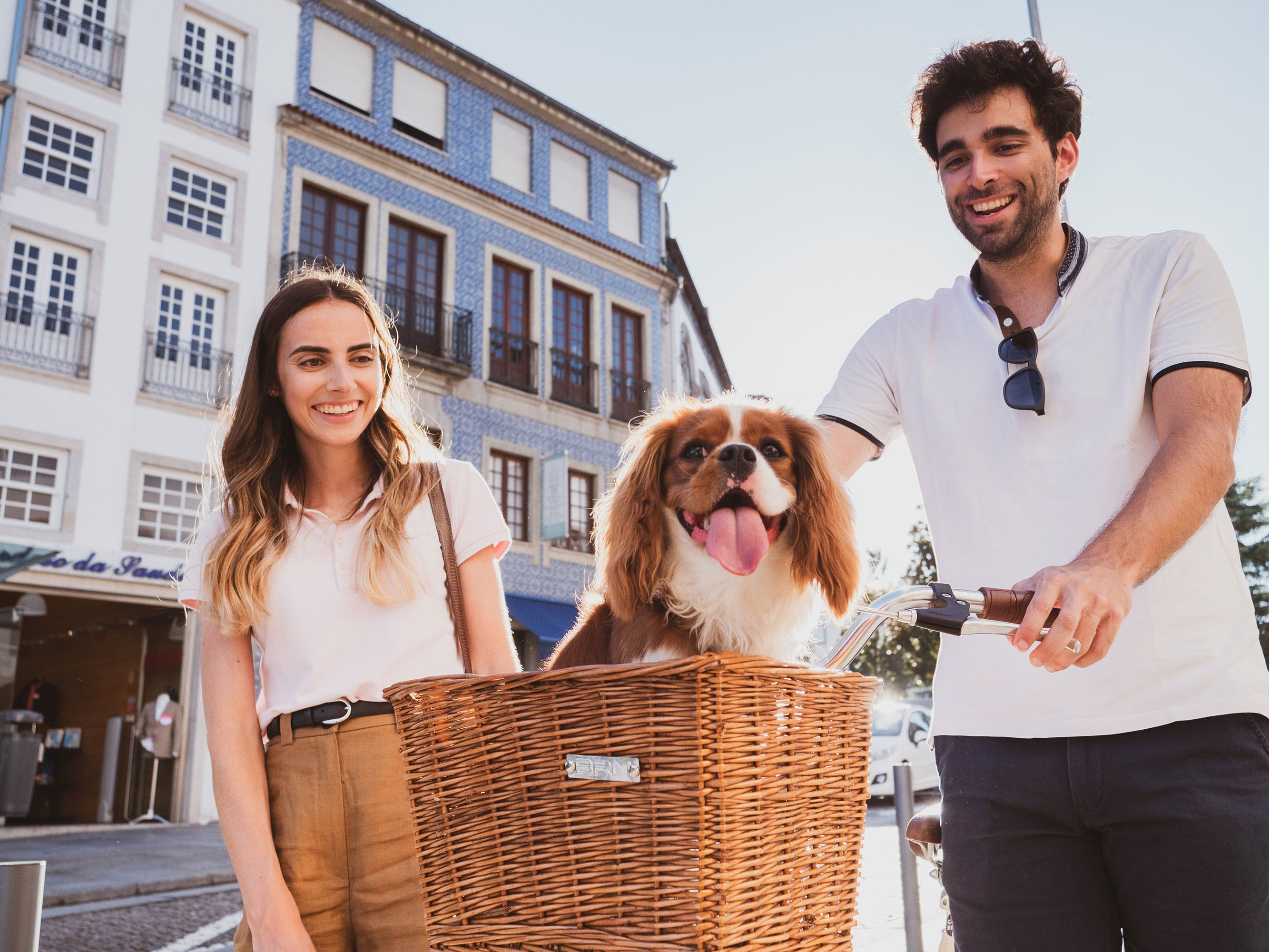 Pareja en bicicleta con su perro de raza King Charles Cavalier