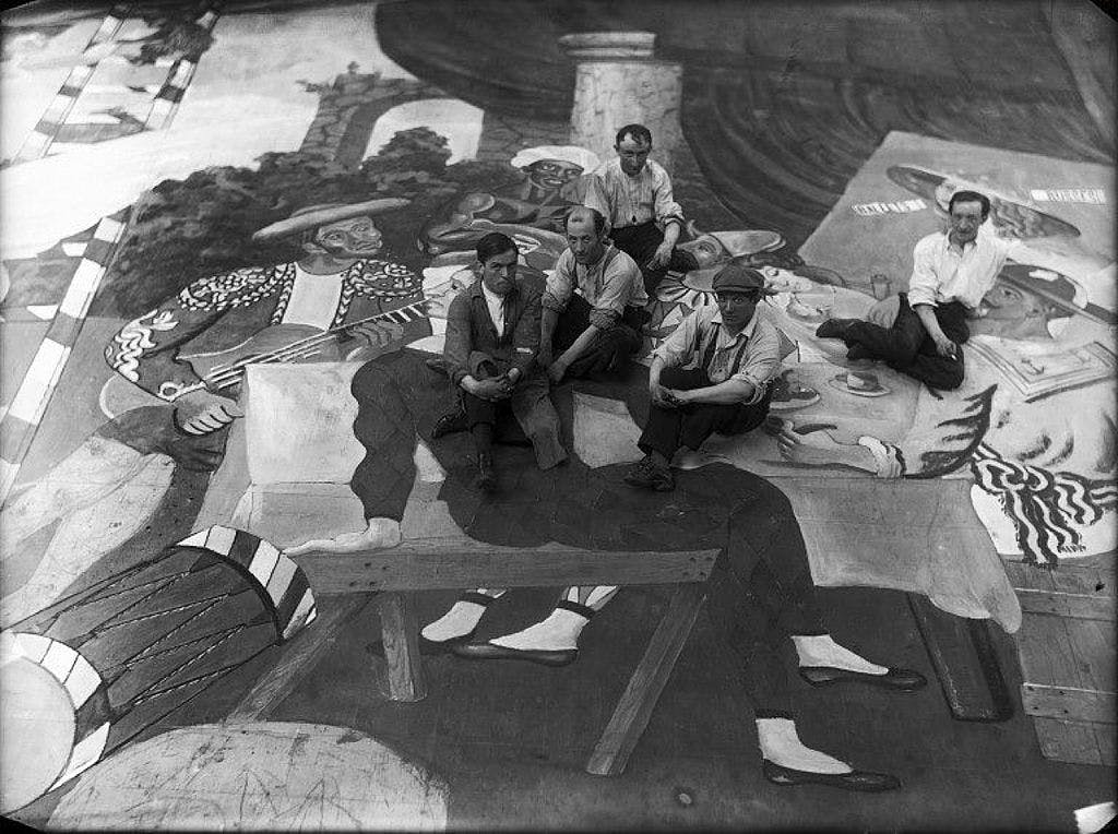 "Pablo Picasso (second from the right, wearing a cap), surrounded by stage workers during the preparations for the ballet ""Parade."" Photo via Wikimedia Commons"