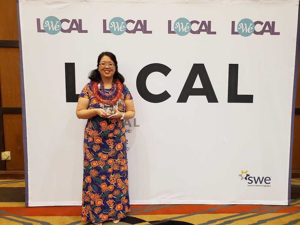 Kristen holding her award in front of the SWE Local sign.