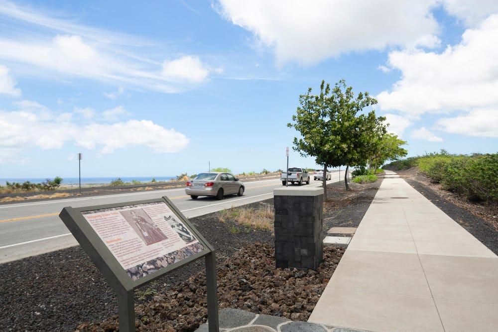 Views of signage and sidewalk alongside highway