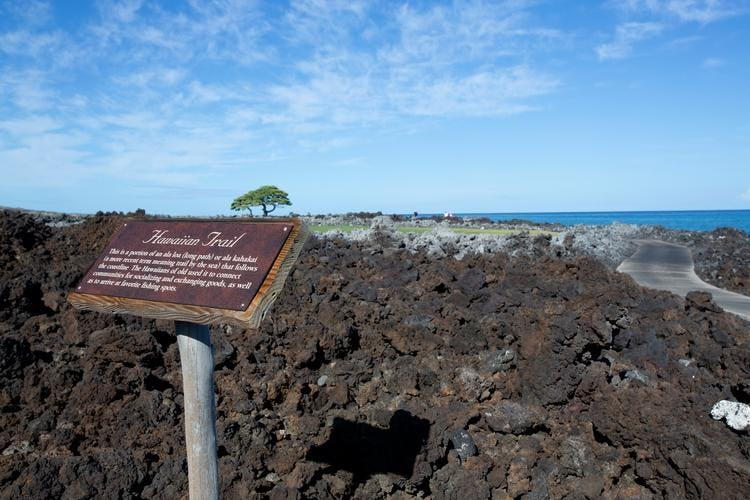 Hawaiian trail signage and view of trail path through lava rocks.