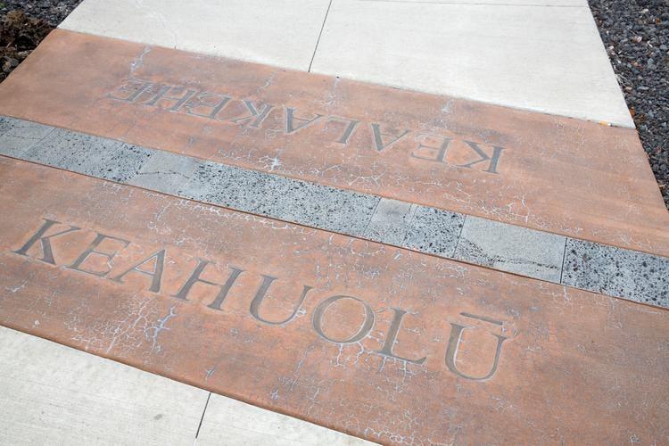Sidewalk marker indicating Keahuolū and Kealakehe ahupua'a boundaries.