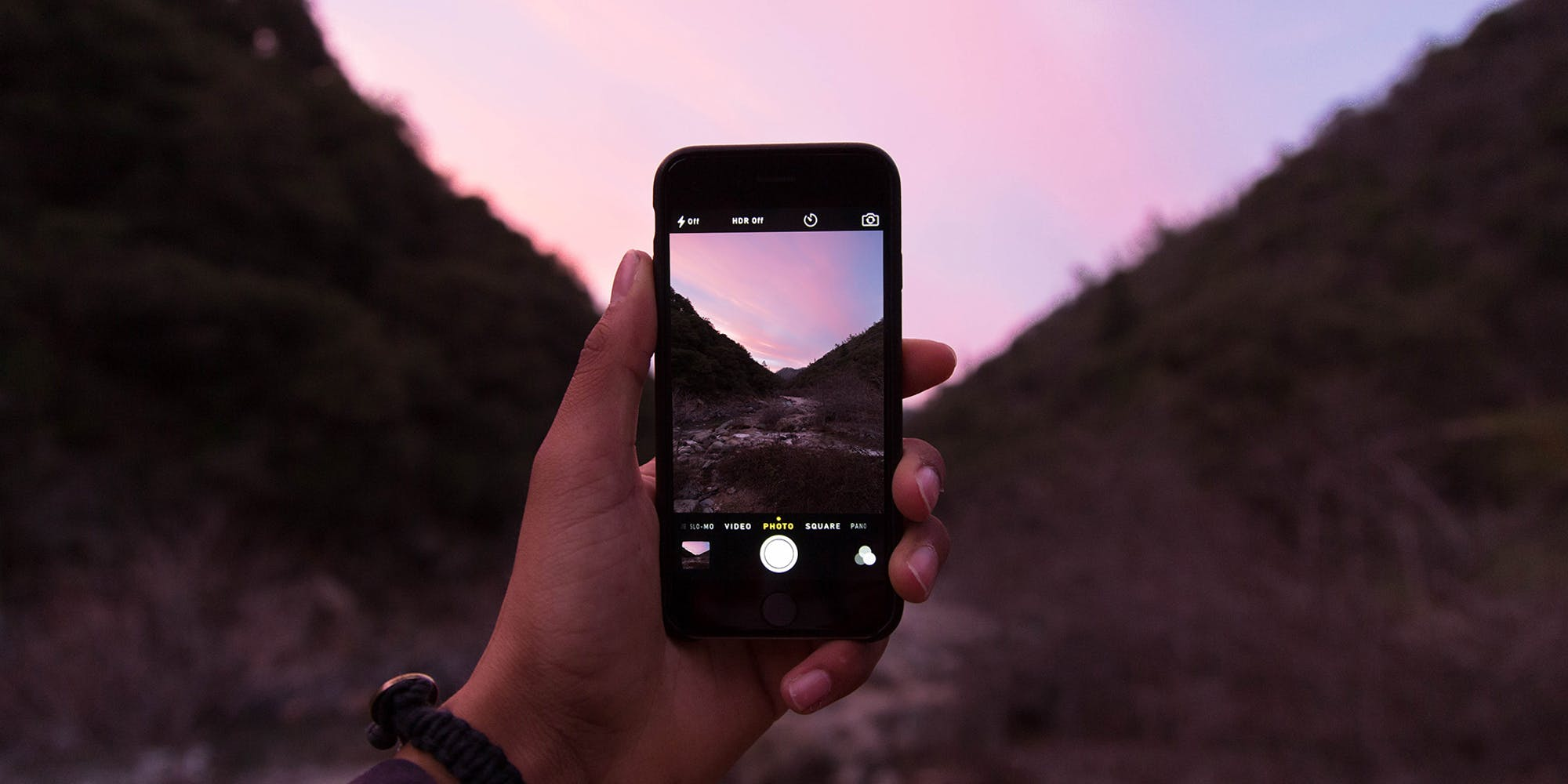Man holding phone taking photo of a valley