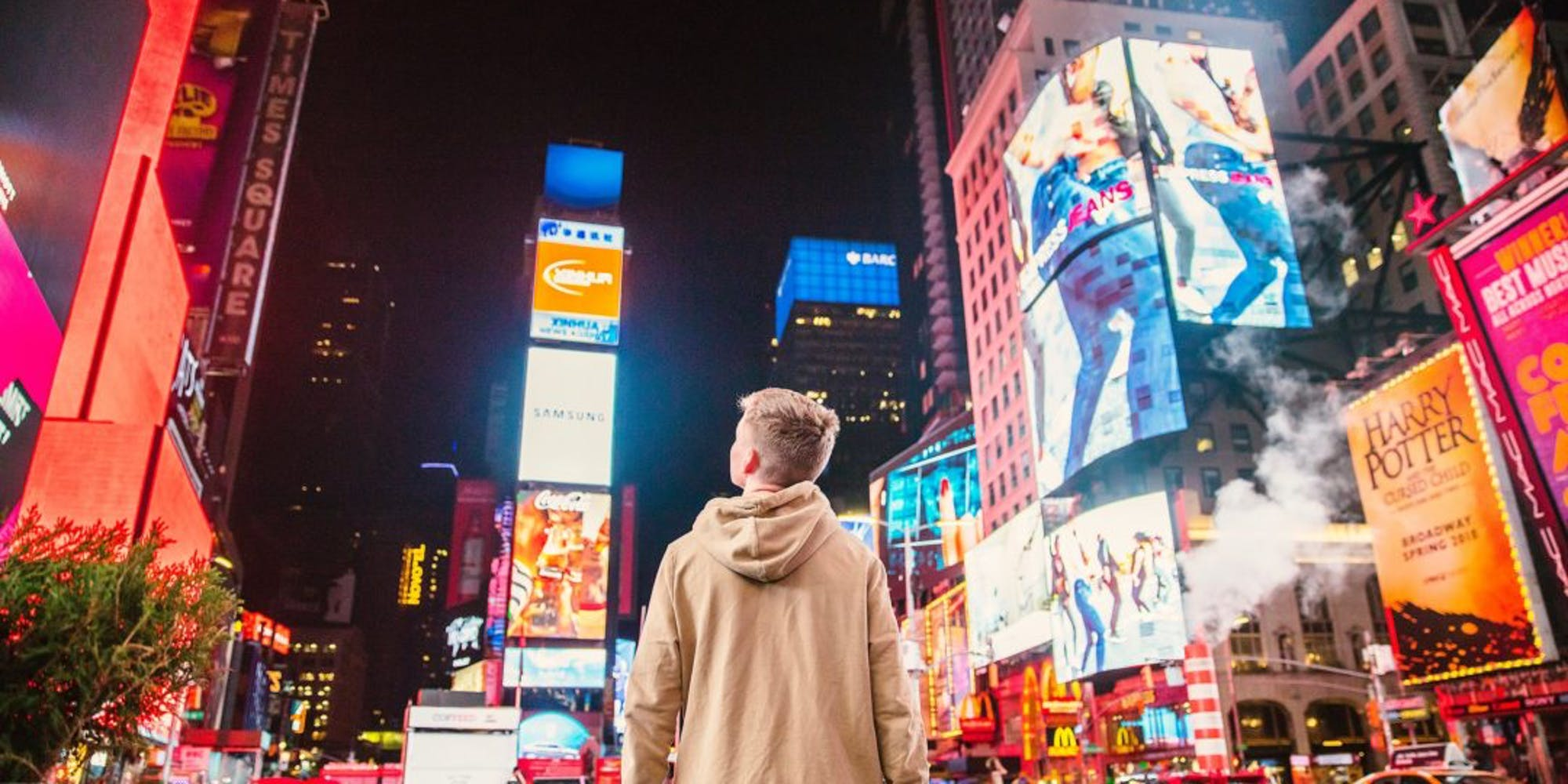 Guy looking out to billboards in the city at night