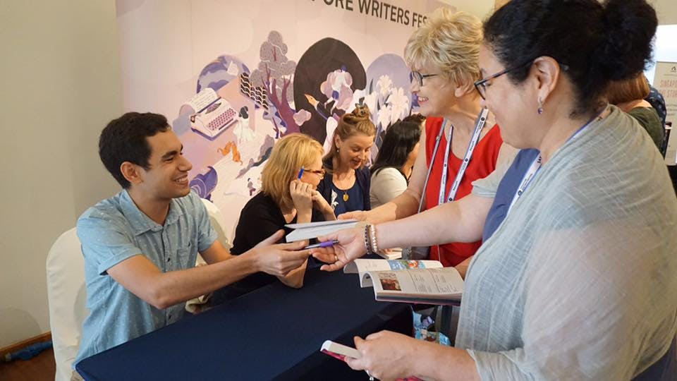 Kane signing books for Singapore Love Stories at Singapore Writers' Festival