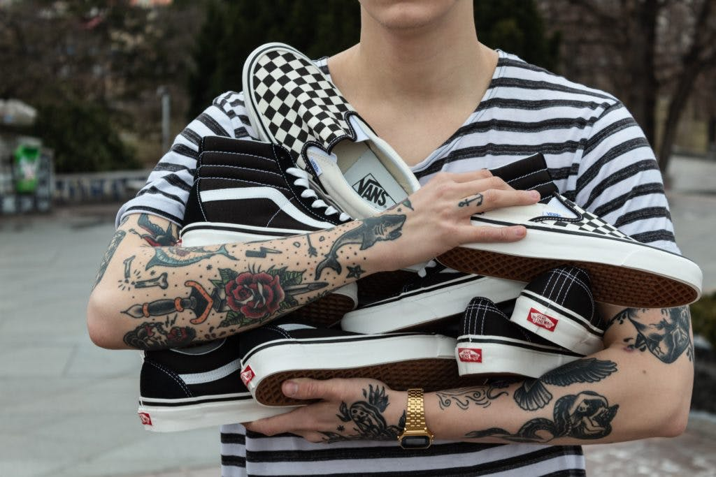 A person with tattooed arms, holding multiple pairs of Vans