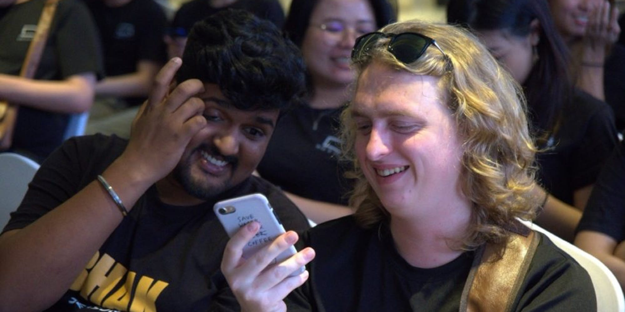 2 guys laughing while looking at their phones
