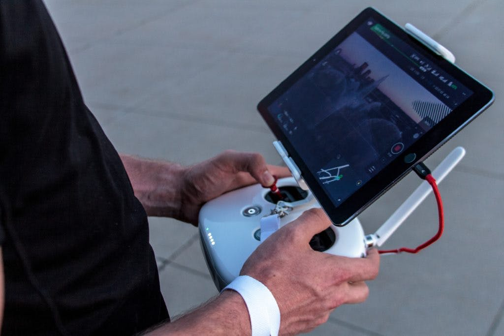 Person operating a drone with an ipad attached to the remote