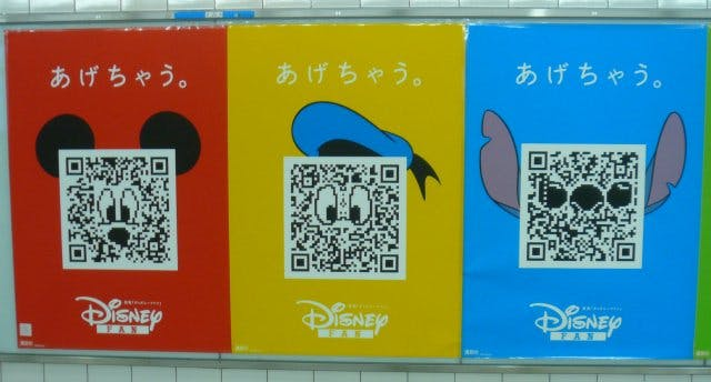 QR code pasted over icons of disney's faces