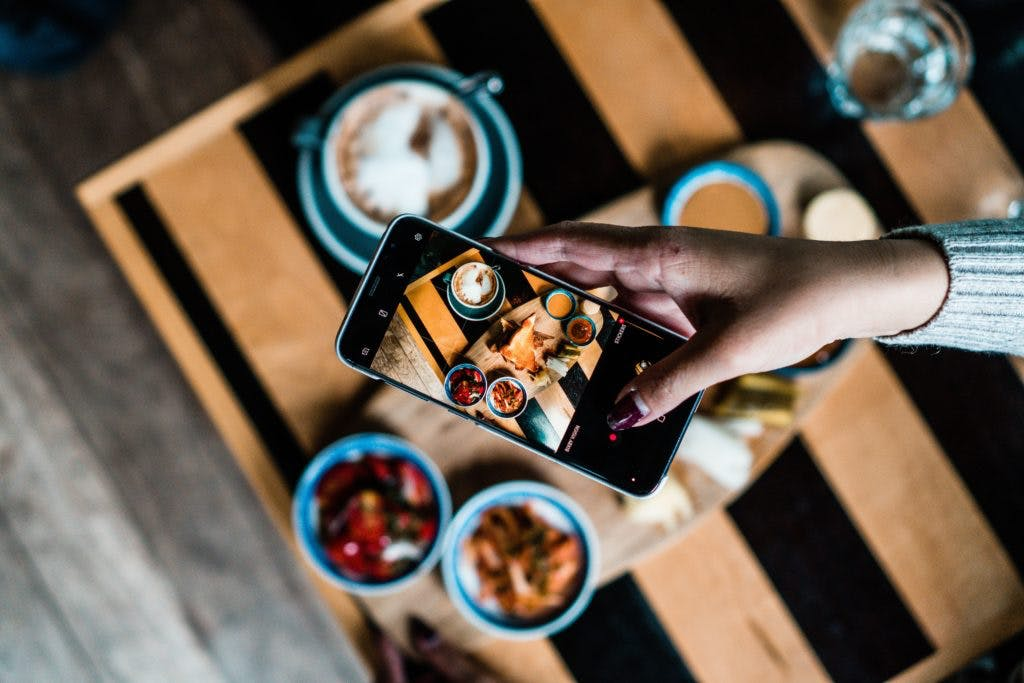 A top shot of a person taking photos of the food displayed on the table