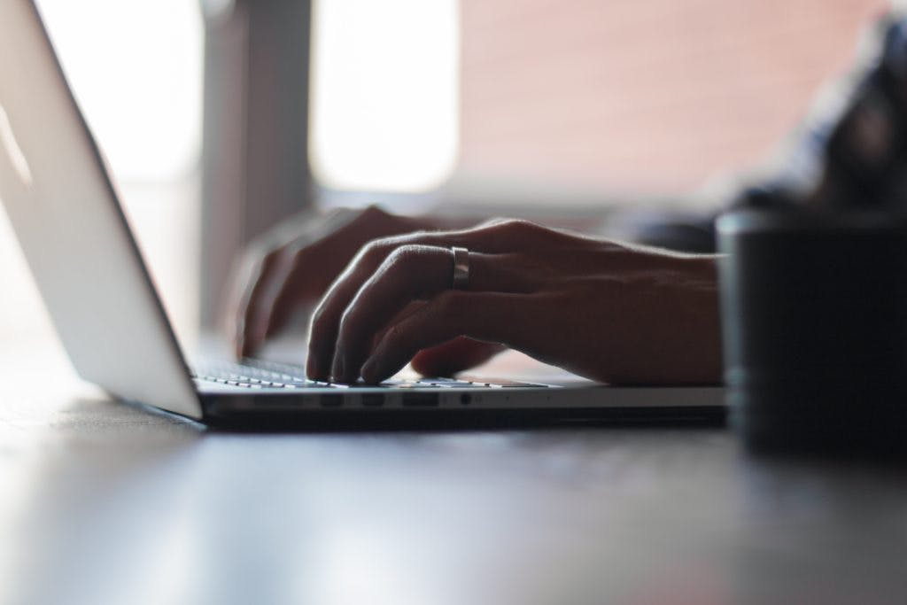 A bokeh shot of a guy using his computer