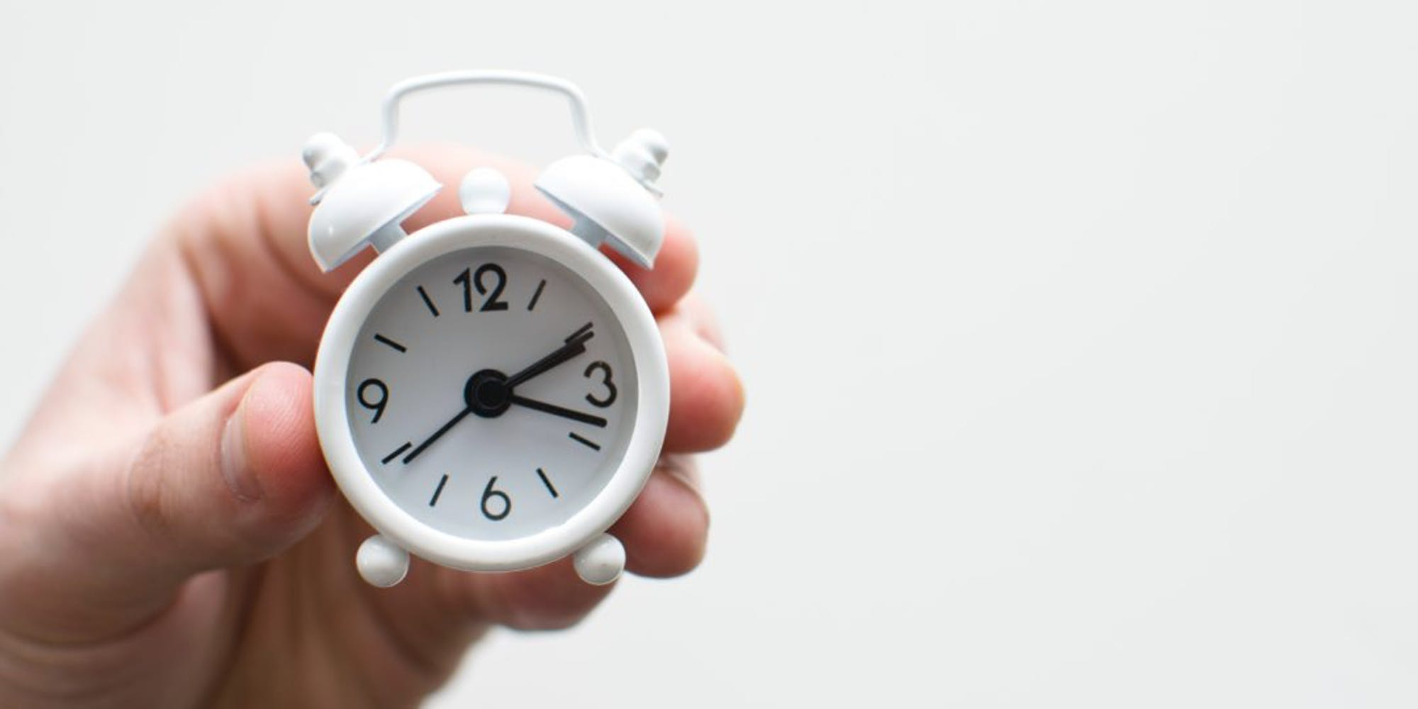 A person holding a tiny alarm clock