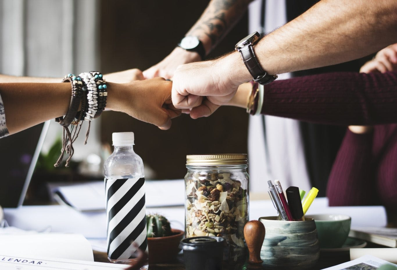 A group of people fist-bumping in a office