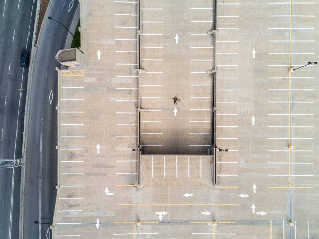 Drone/aerial shot of a person lying in the middle of an empty carpark