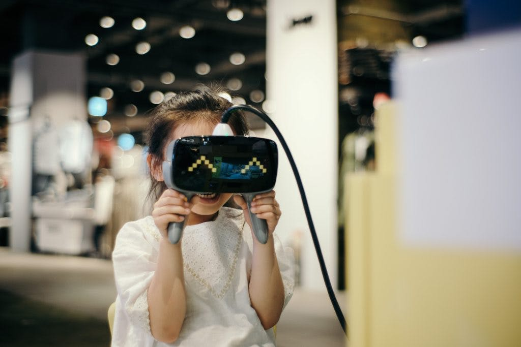Little girl holding a VR device over her face