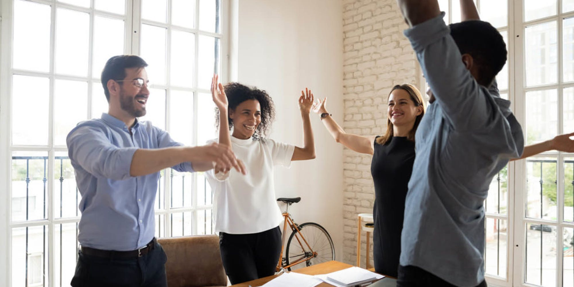 4 people raising their hands, celebrating in an office