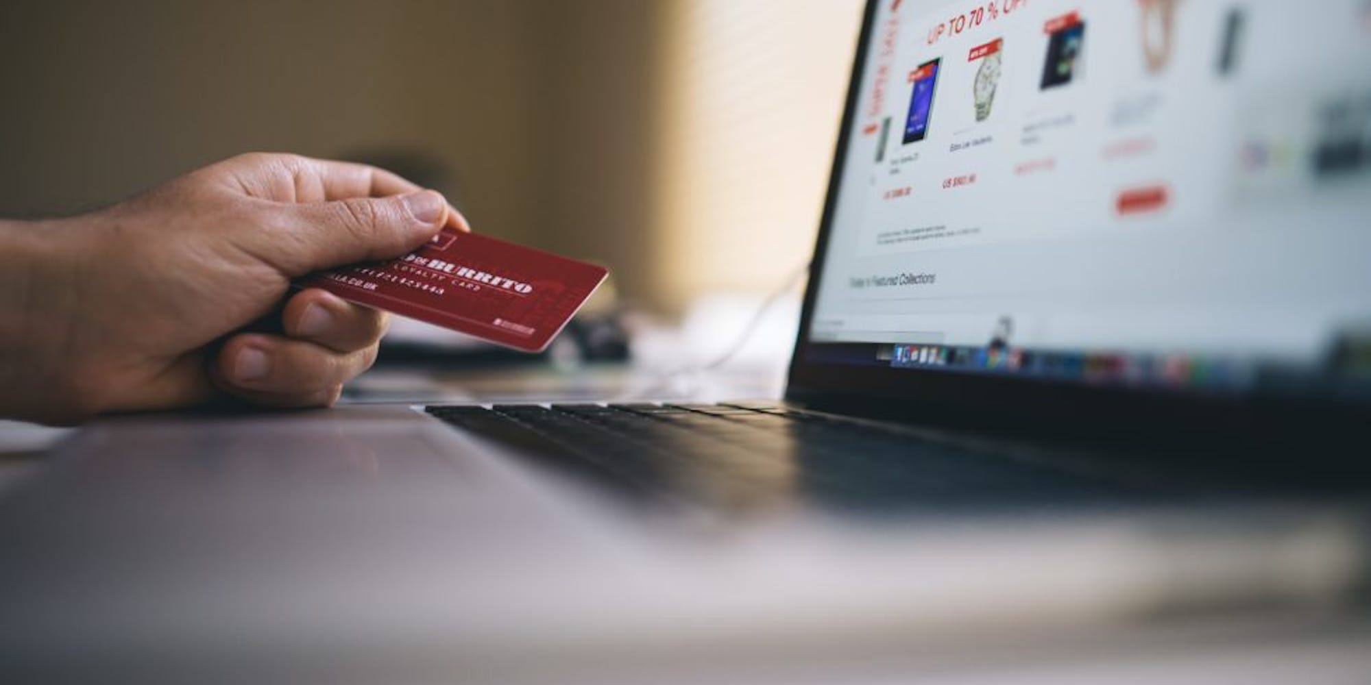 Person holding a credit card, intending to purchase something on the internet