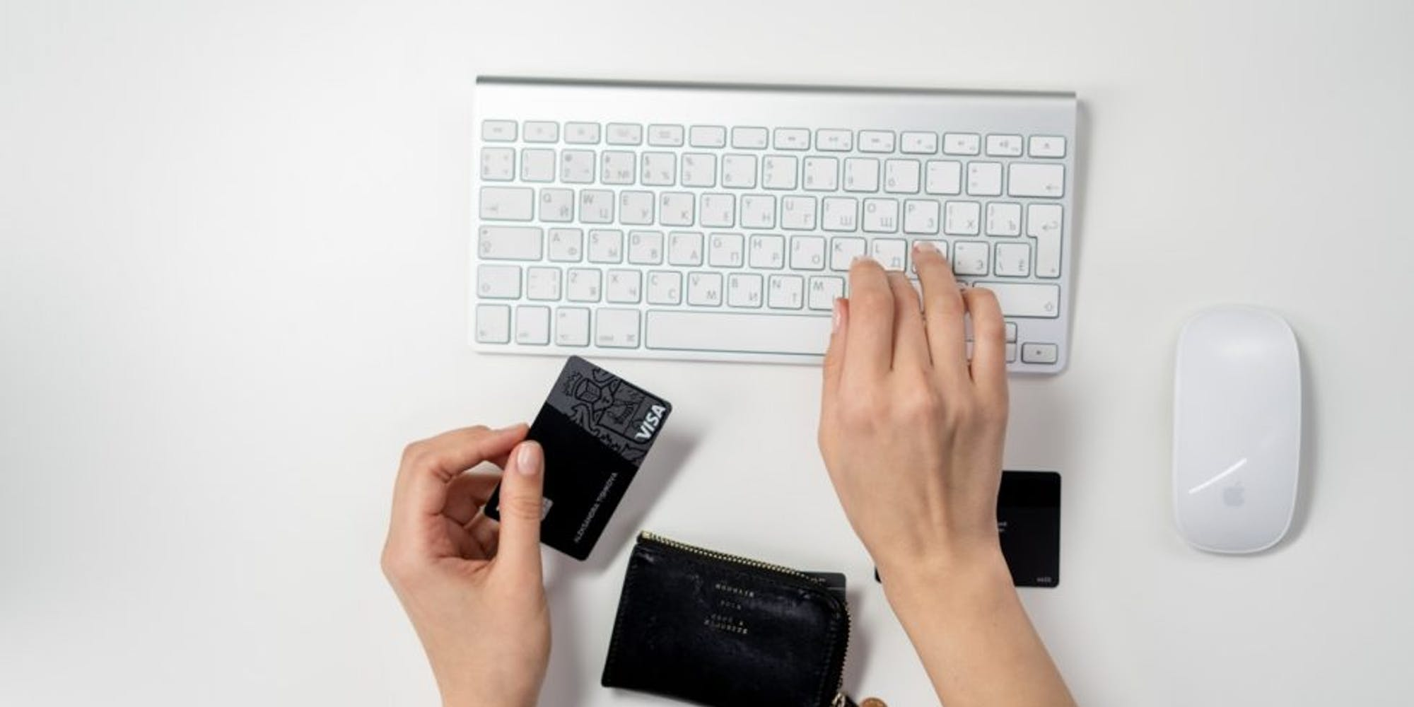 Lady keying her credit card details on an Apple keyborad