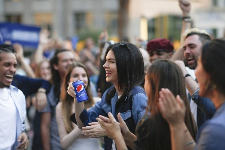 Kendall Jenner holding a Pepsi can in the middle of a crowd