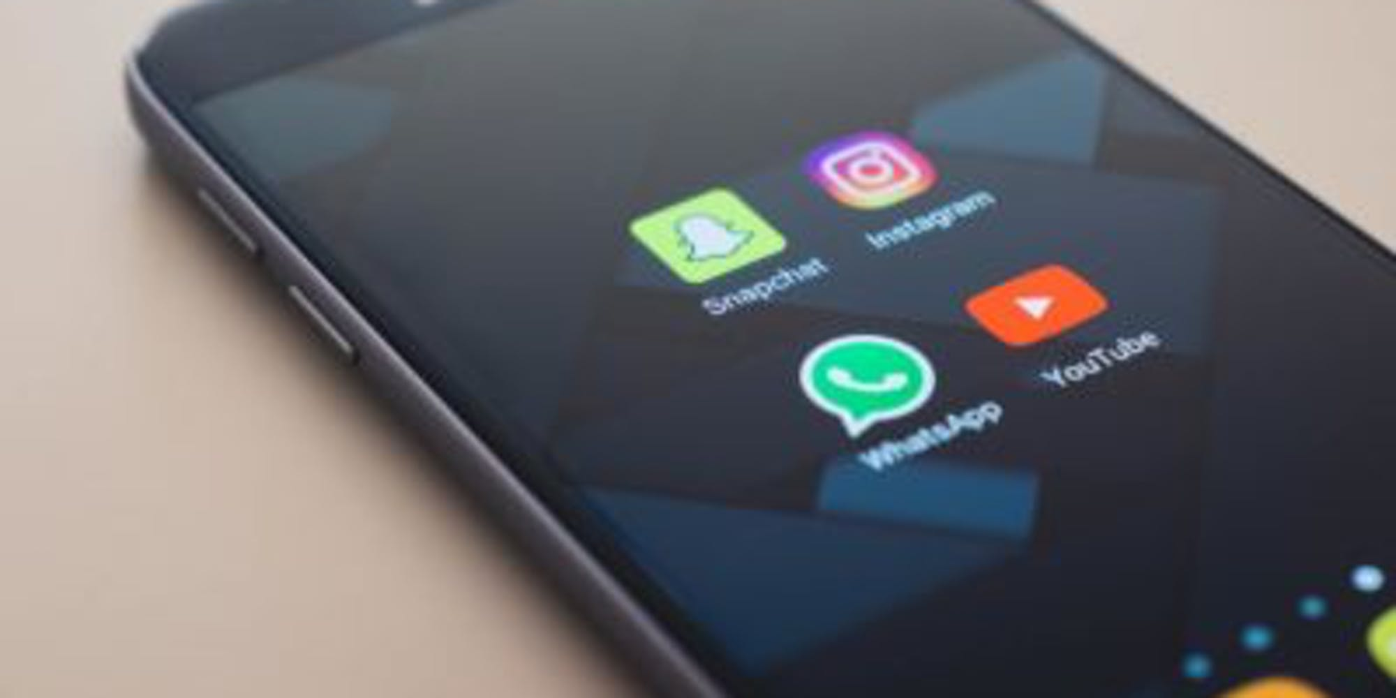 A phone opening up to a folder with social media apps Snapchat, Instagram, Whatsapp and Youtube