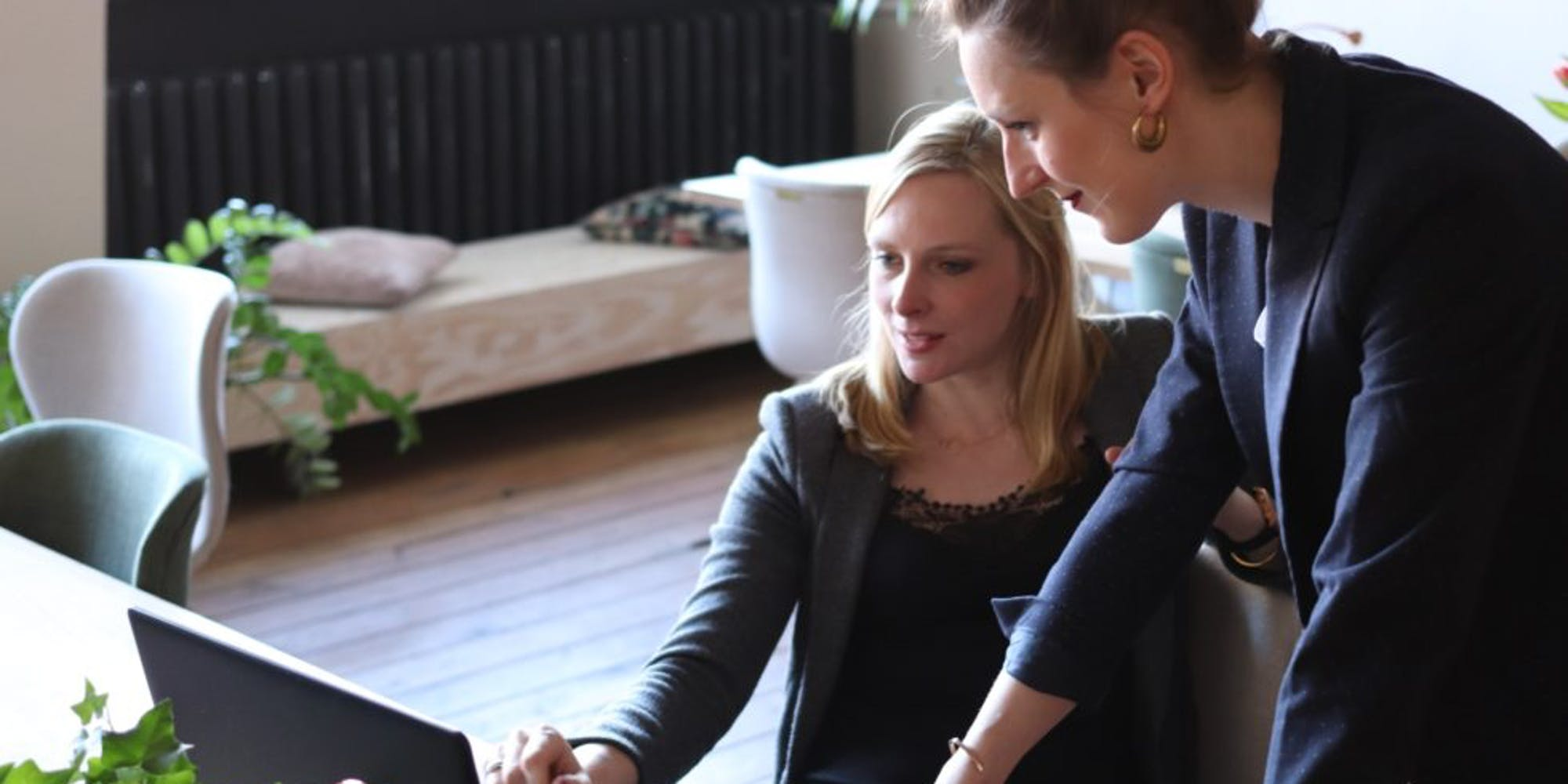 Two women looking at a laptop together discussing