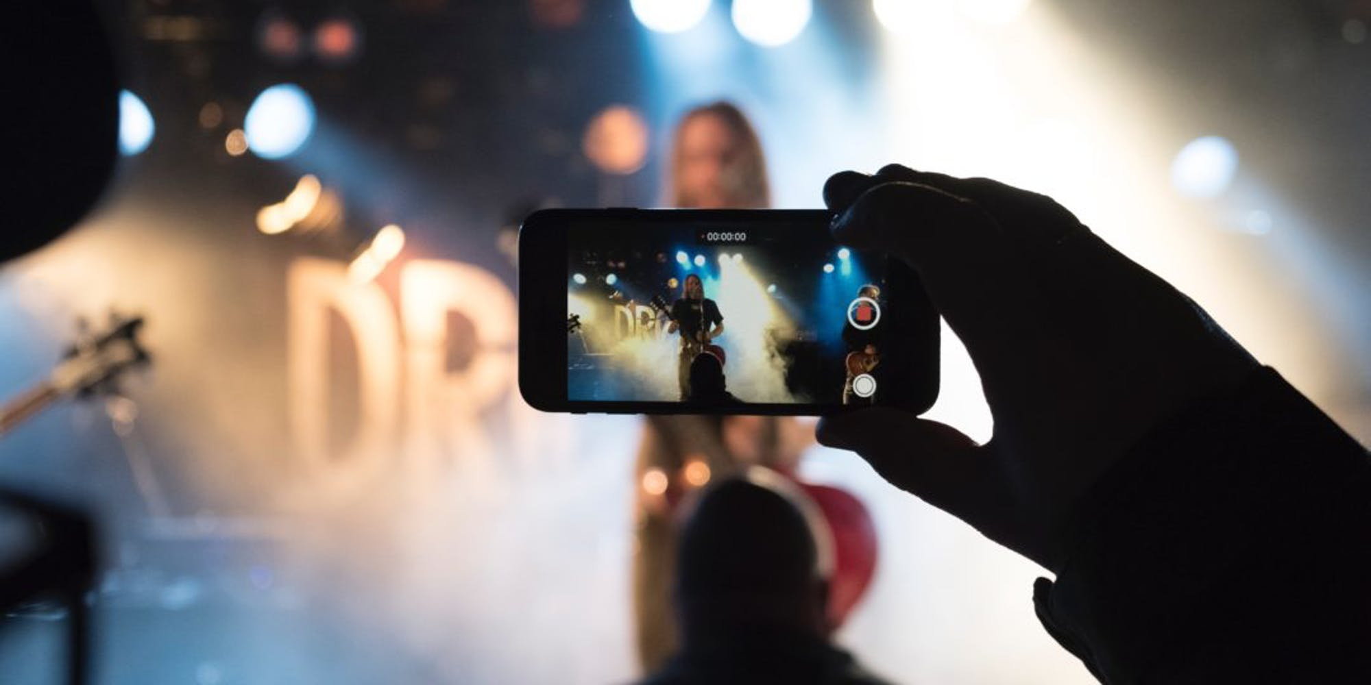 A person recording a video of a concert