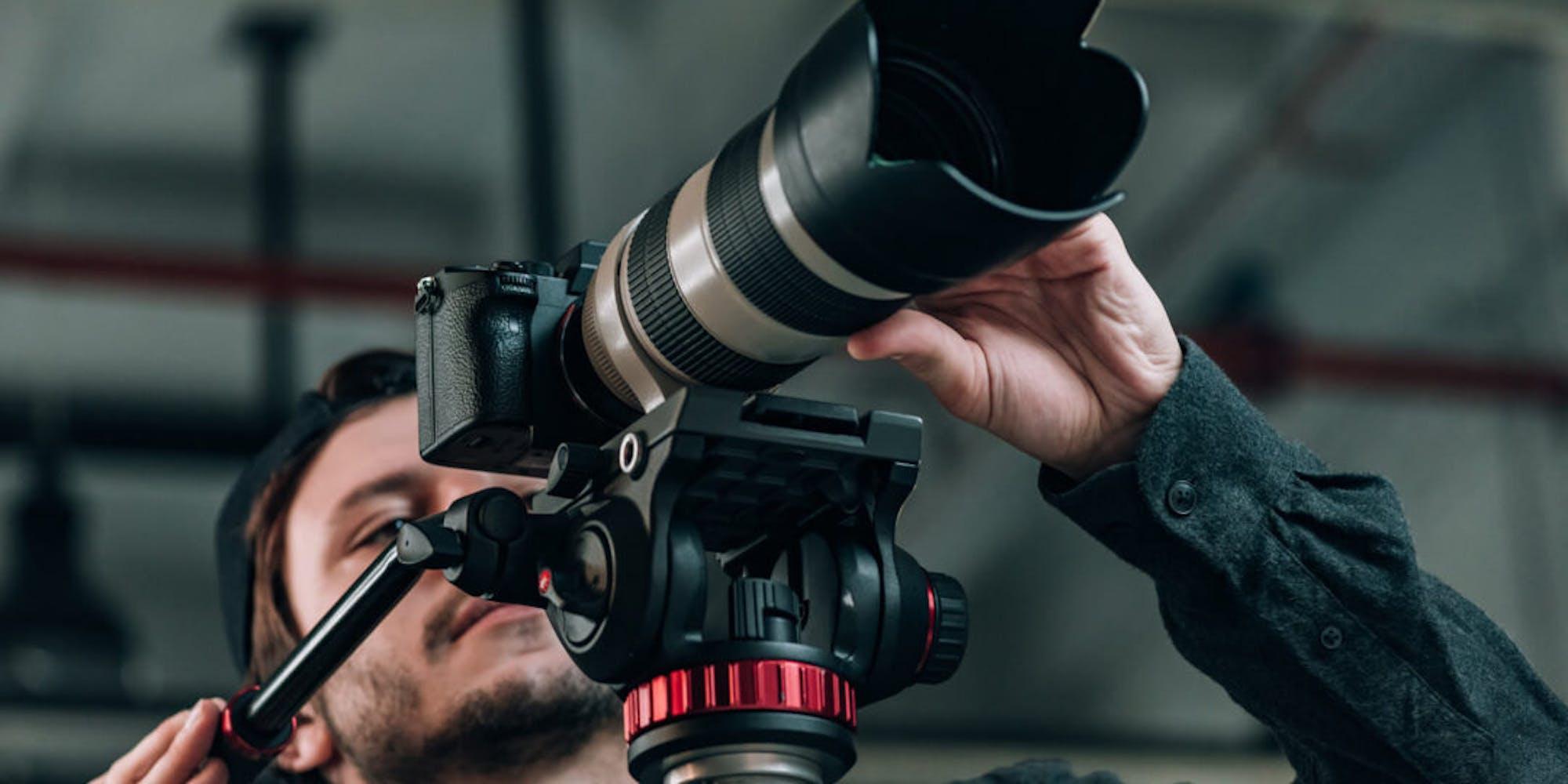 A guy using a camera on tripod