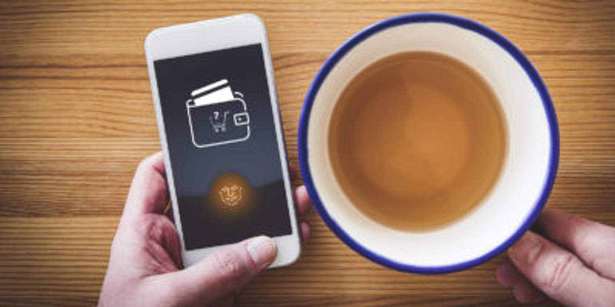 Person drinking tea and paying for it through their smartphone