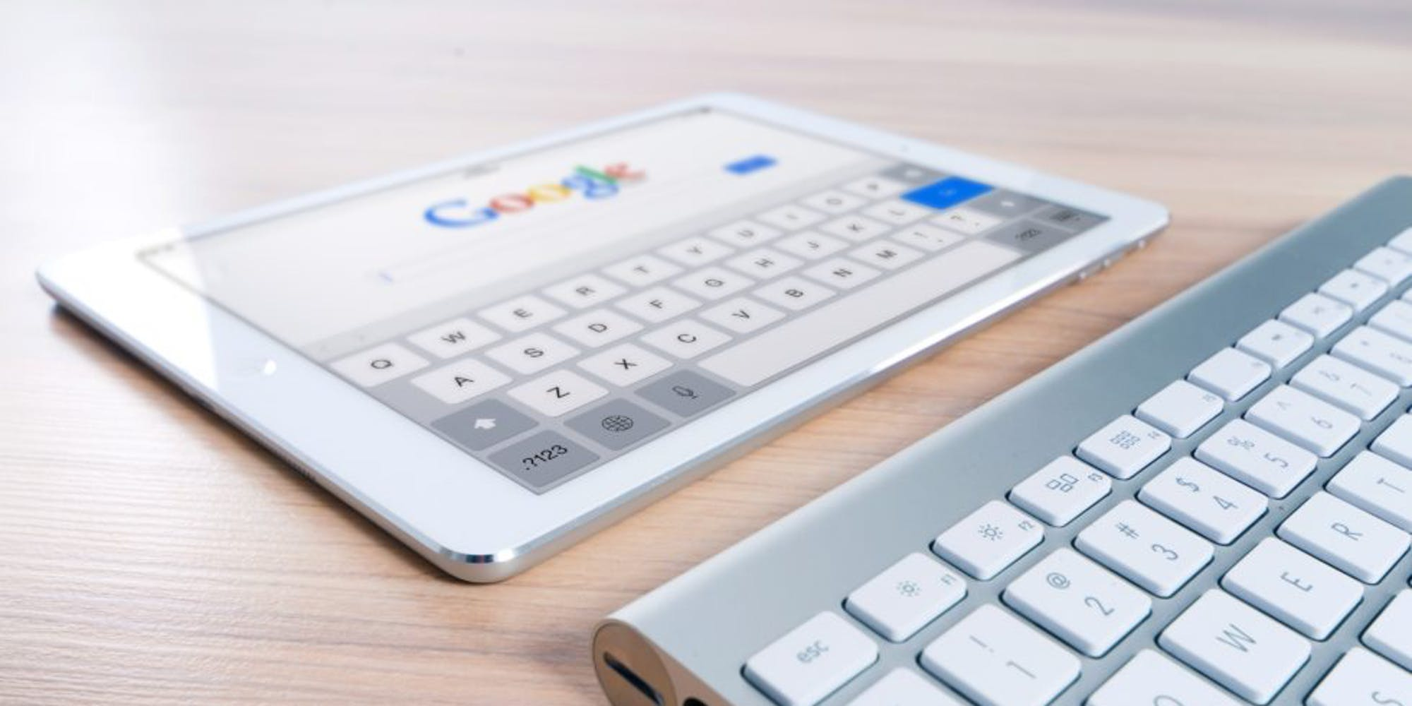 A tablet displaying Google's search engine, with a keyboard next to it