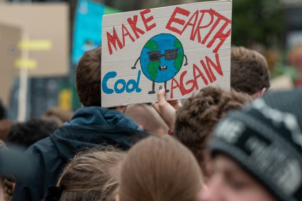 "A guy holding a ""Make earth cool again"" sign in the middle of the crowd"