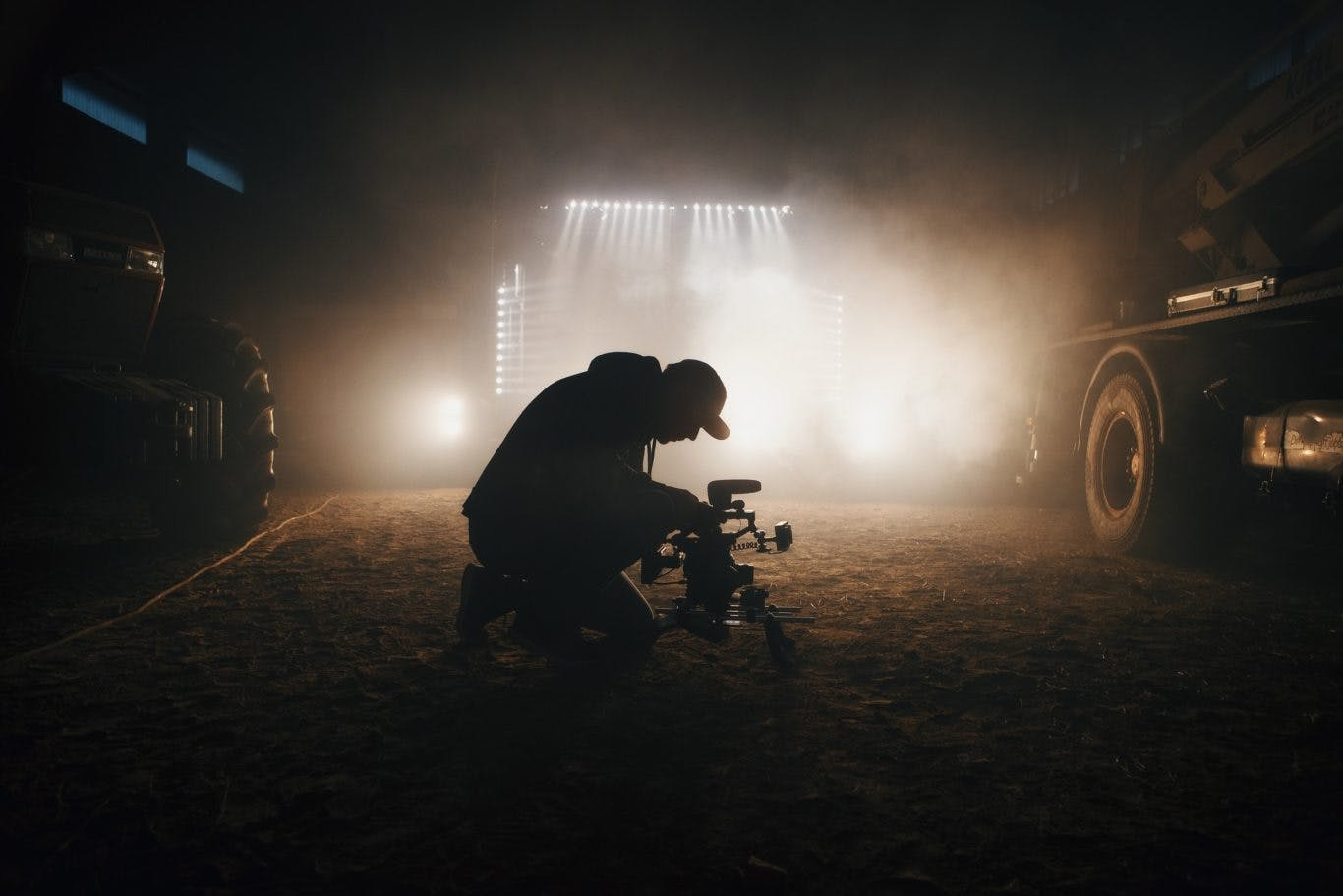 Guy filming trucks in a warehouse with foggy lights