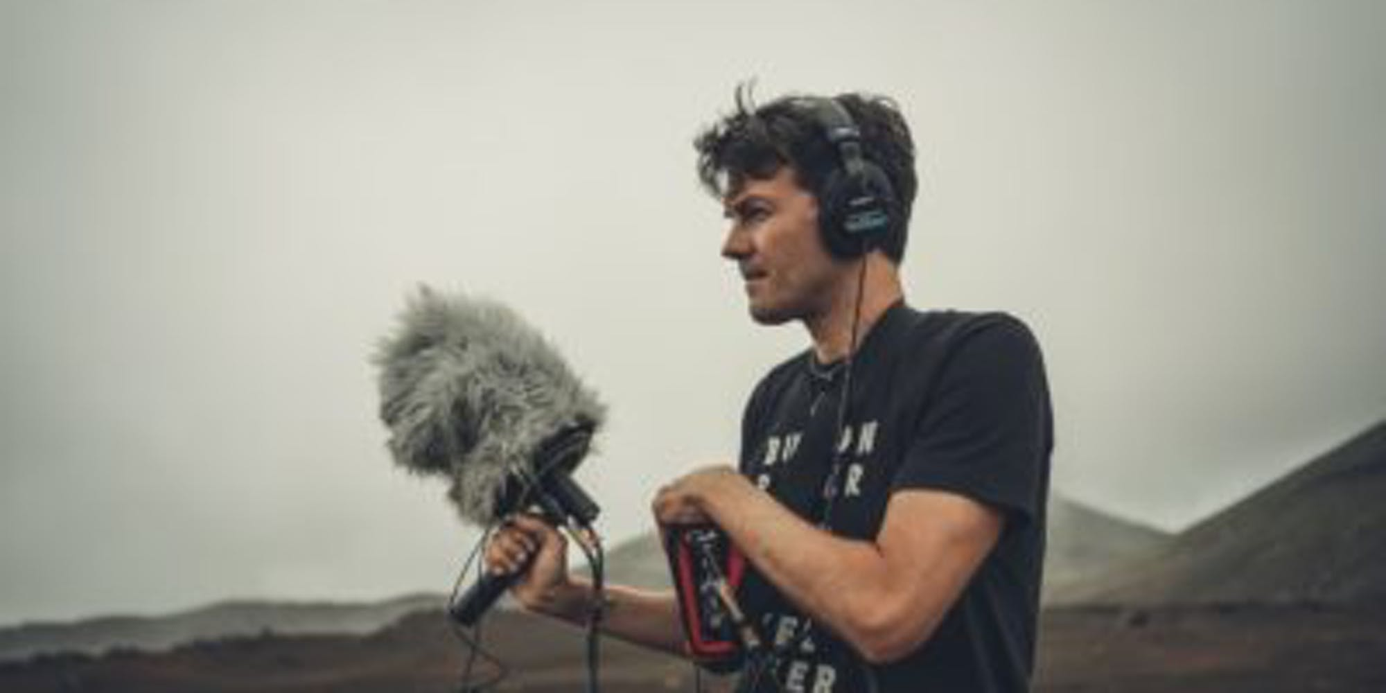Man holding a boom mike prepared to record audio